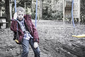 Bullied boy sitting on swing chair