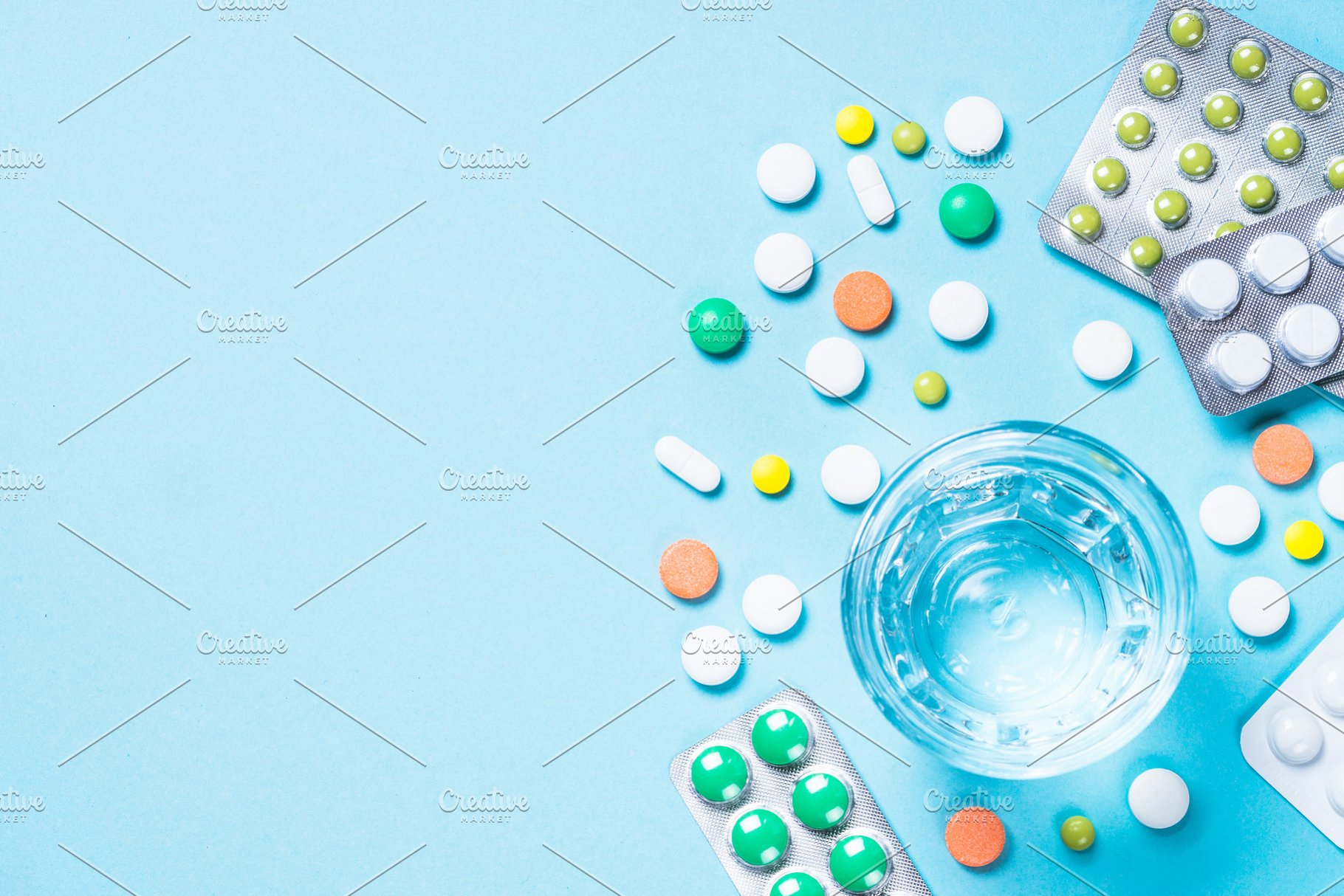 Pills and glass of water on blue top