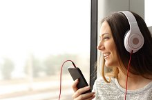 Teen passenger listening to the music traveling in a train.jpg