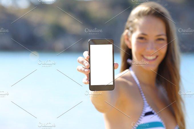 Sunbather showing blank phone screen on the beach.jpg - Technology