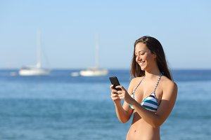Sunbather girl using a smart phone on summer holidays.jpg