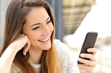 Woman browsing media in a mobile phone.jpg