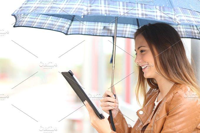 Woman reading ebook or tablet under the rain.jpg - Technology