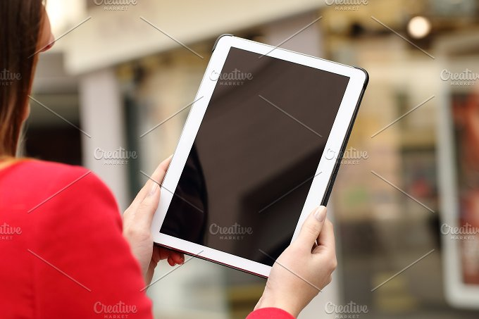 Woman using and showing a blank tablet screen.jpg - Technology
