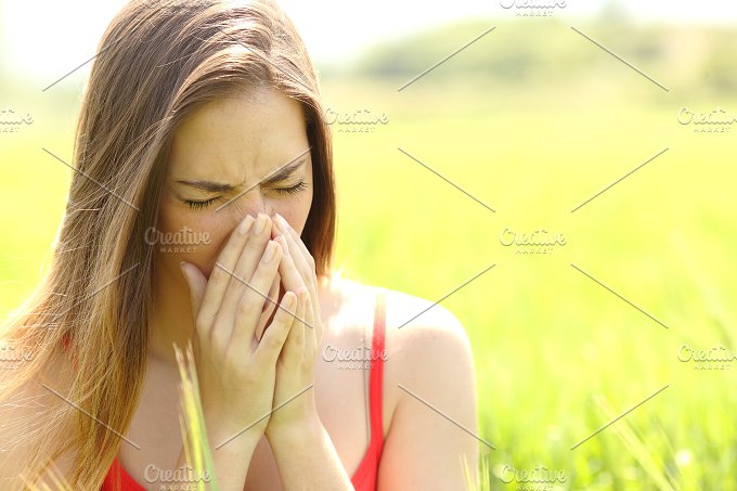 Woman with allergy coughing in a field.jpg - Health