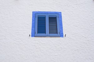 Blue window on a white wall