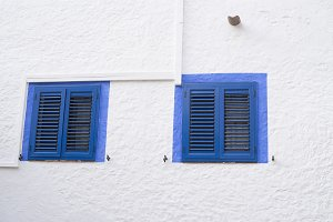 Two blue windows on a white wall