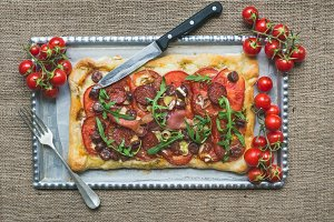 Rustic meat pizza with tomatoes