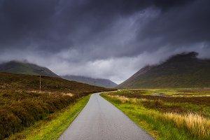 Road in the fields, dark cloudy sky