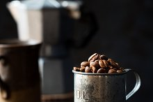 Coffee beans in a tin measuring cup by  in Food & Drink