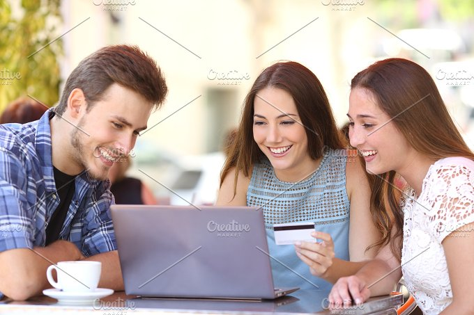 Friends shopping online with a credit card and a laptop.jpg - Technology