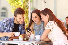 Friends watching media in a smart phone in a coffee shop.jpg
