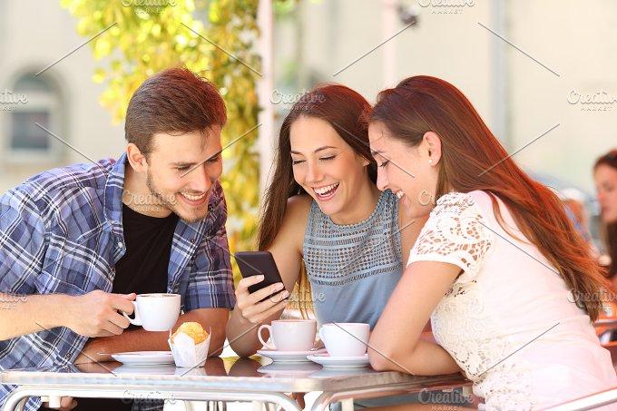 Friends watching media in a smart phone in a coffee shop.jpg - Technology
