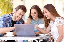 Friends watching videos in a laptop in a coffee shop.jpg