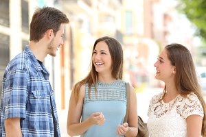 Three friends talking taking a conversation on the street.jpg