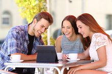 Three friends watching tv or social media in a tablet.jpg