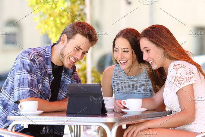 Three friends watching tv or social media in a tablet.jpg - Technology