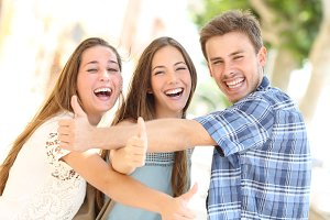 Three happy teenagers laughing with thumbs up.jpg