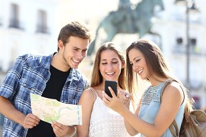 Three tourist friends consulting gps on smart phone.jpg