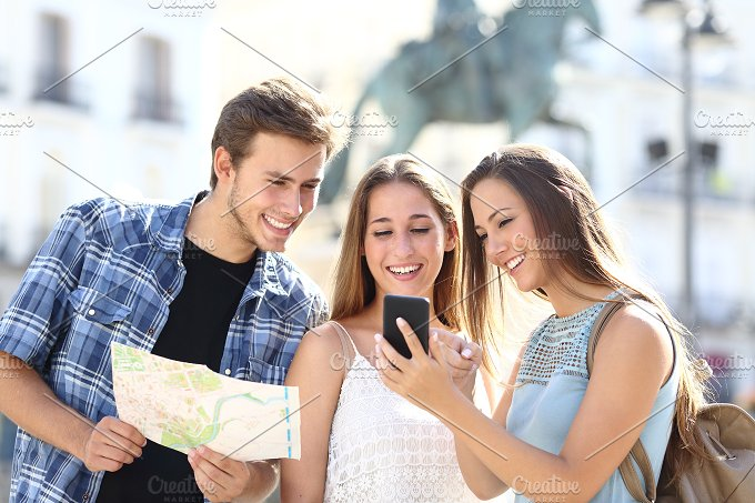 Three tourist friends consulting gps on smart phone.jpg - Holidays