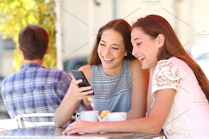 Two friends or family sharing a smart phone in a coffee shop.jpg - Technology