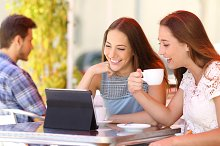 Two friends or sisters watching videos in a tablet.jpg