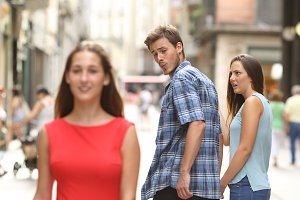 Unfaithful man with his girlfriend looking at another girl.jpg