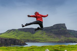 Man jumping in the green meadows