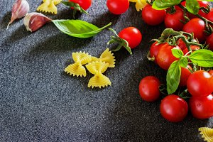 fresh organic cherry tomatoes and paste with basil garlic on a dark background.