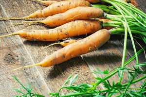 Fresh Organic Carrots on wooden background.