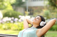 Woman listening to music and relaxing in a park.jpg