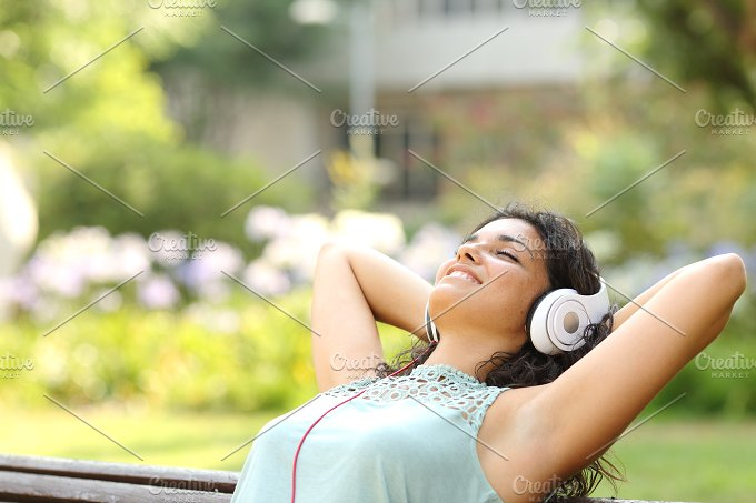 Woman listening to music and relaxing in a park.jpg - Technology