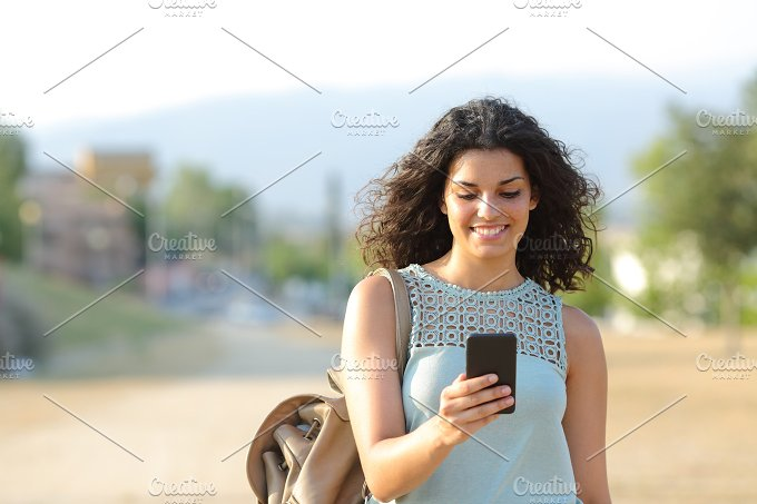 Girl walking and using a smart phone in a town.jpg - Technology