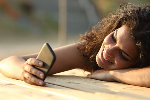 Woman watching social media in a smart phone at sunset.jpg