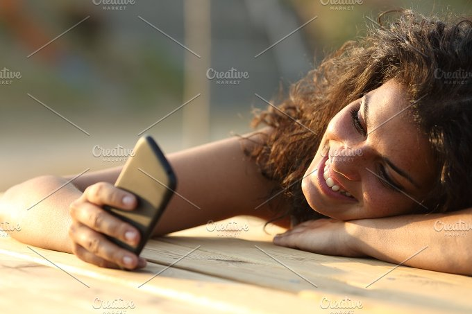 Woman watching social media in a smart phone at sunset.jpg - Technology