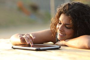 Woman using a tablet touching screen at sunset.jpg