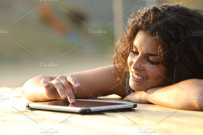 Woman using a tablet touching screen at sunset.jpg - Technology
