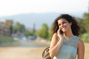 Woman talking on the phone walking in a park.jpg