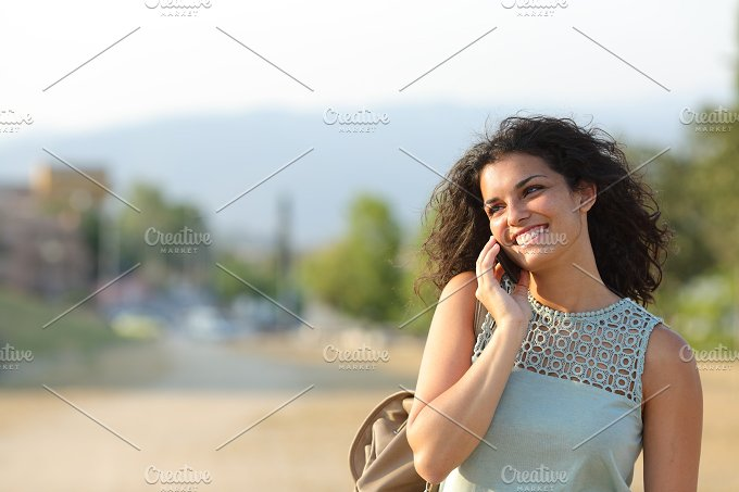 Woman talking on the phone walking in a park.jpg - Technology
