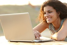 Woman using a laptop in a park at sunset.jpg