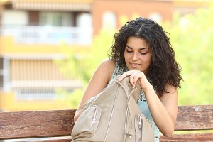 Woman searching something in her hand bag.jpg