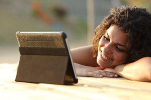 Woman watching videos on a tablet at sunset.jpg
