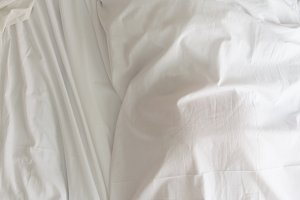 young woman sleeping on the white linen in bed at home,