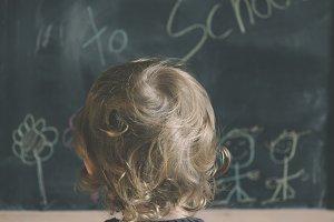 Cheerful little boy on blackboard