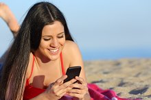 Teen girl texting on the smart phone on the beach.jpg