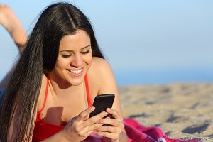 Teen girl texting on the smart phone on the beach.jpg