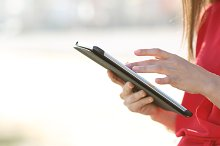 Woman hands browsing a tablet outdoors.jpg