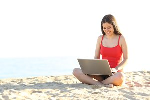 Teen student using a laptop on the beach.jpg