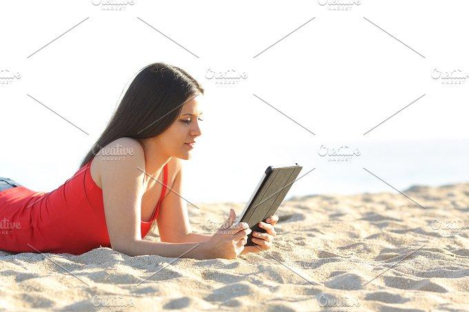 Girl reading an ebook or tablet on the beach.jpg - Technology