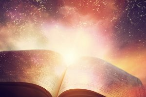 Open old book merged with galaxy sky